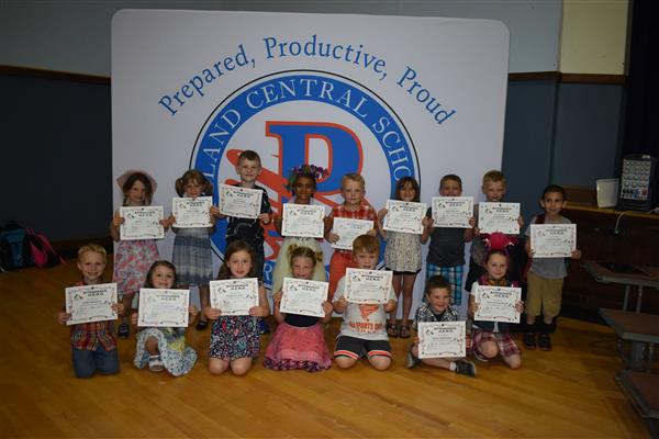 Kindergarteners holding their attendance awards