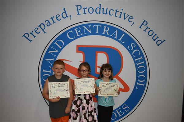First-graders holding their attendance awards