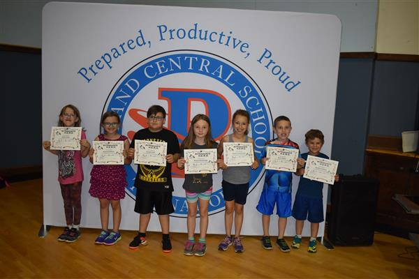 Second-graders holding their attendance awards