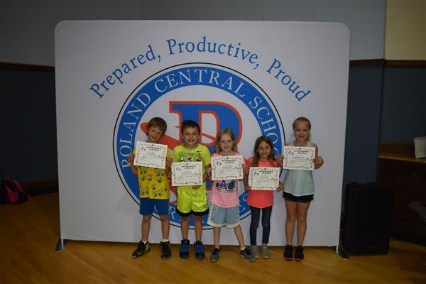 Third-graders holding their attendance awards