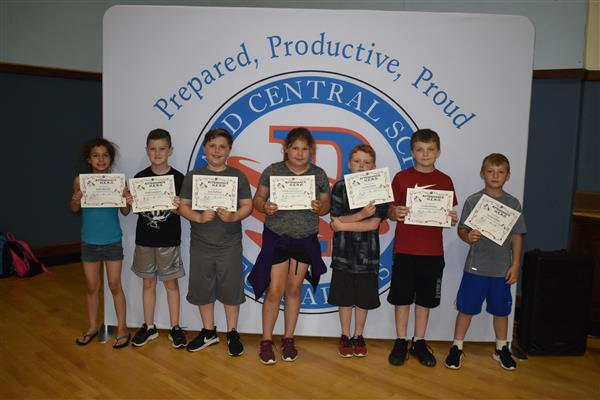 Fourth-graders holding their attendance awards