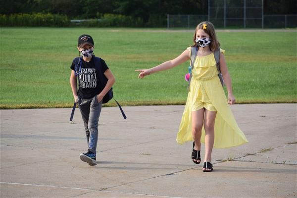 Two students walking toward the school building wearing cow pattern masks on first day of school