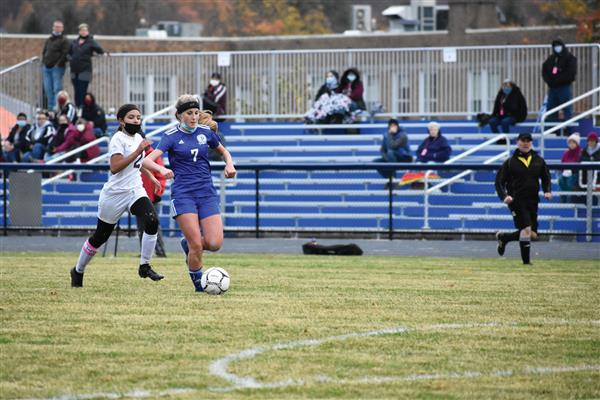 Lexi Bates dribbles the soccer ball during first game on new field with a Frankfort-Schuyler player behind her