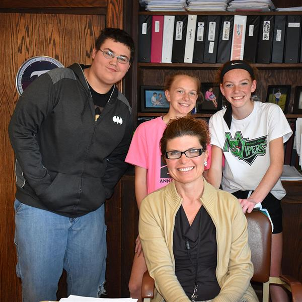 Poland math teacher Stacey Bennett at her desk surrounded by three students