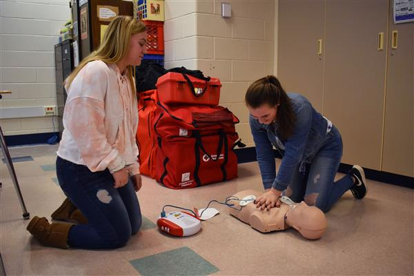 Two students practicing CPR on a mannequin in class
