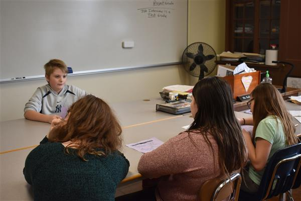 Student sitting at desk as three students interview him