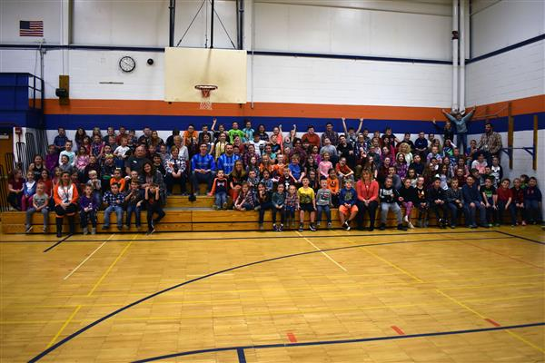 Utica City FC soccer players pose with a large group of Poland elementary students