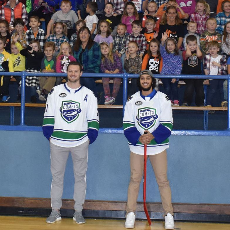 Utica Comets hockey players standing in front of elementary students and teachers in stands