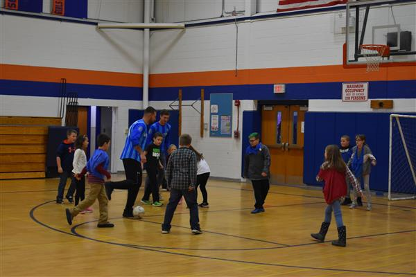 Utica City FC soccer players playing with Poland students