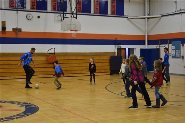 Utica City FC soccer players playing soccer with Poland students
