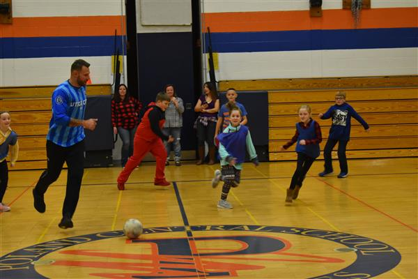 A Utica City FC soccer player dribbles the ball as students run around nearby