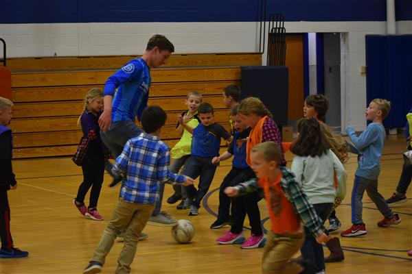 Students crowd around a Utica City FC soccer player dribbling the soccer ball