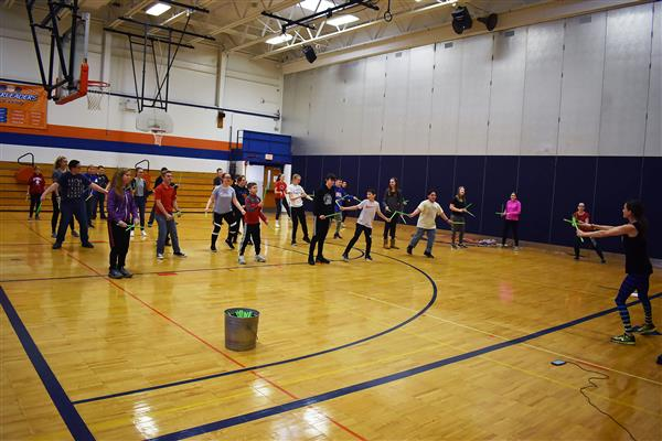 Students hit green sticks together during POUND fitness activity