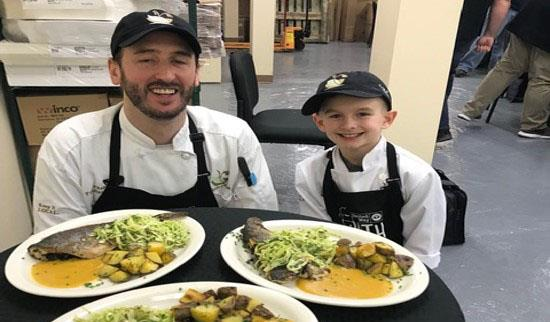 Elijah and chef teammate display their signature dish