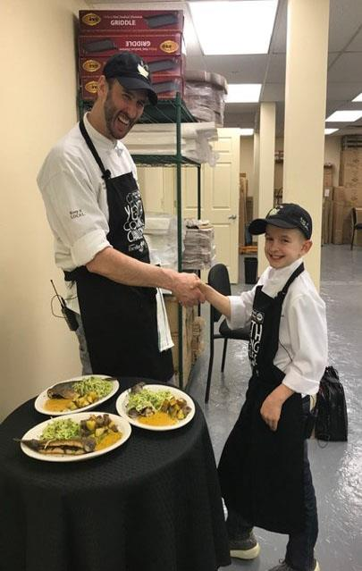 Elijah and his chef teammate shake hands by their signature dish