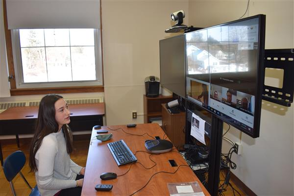 Maddison Haver speaking to a panel of judges virtually on a screen in a Poland classroom