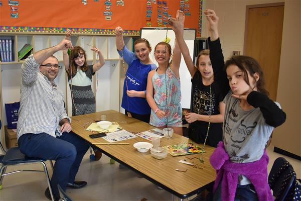 Michael Gagnon and Kids Against Pollution, Poverty and Prejudice club members hold up strings of beads