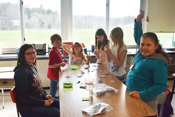 Kids Against Pollution, Poverty and Prejudice club members hold up and work on strings of beads
