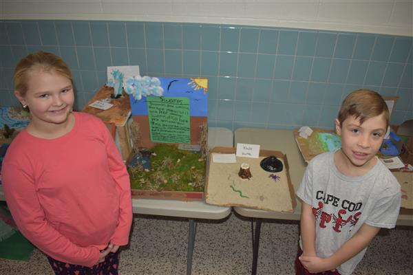 Student poses with her swamp project and another with his butte project