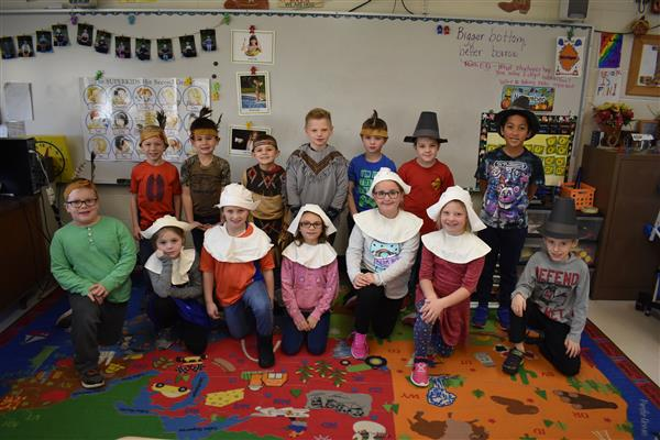 Second-graders in Pilgrim and Native American costumes pose as a group for Thanksgiving activity