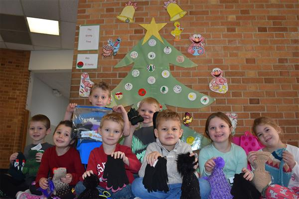 Poland kindergarteners holding donated warm winter accessories in front of the giving tree