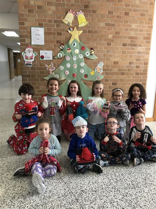 Poland elementary students holding winter clothing items that were donated