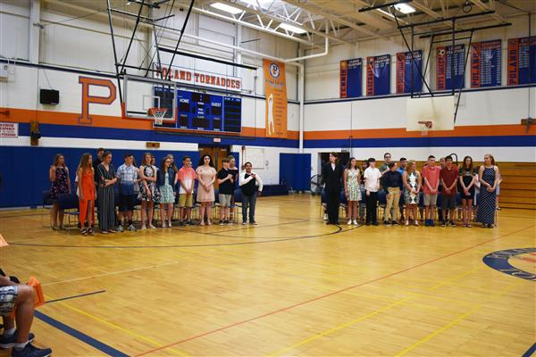 Poland eighth-graders standing in the gym at the beginning of Moving Up Ceremony