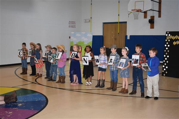 Students holding up the letters of the word champion during their class play