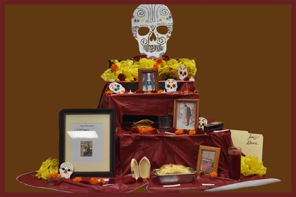 An ofrenda or altar display with red colors and skulls and images of a student who did the project
