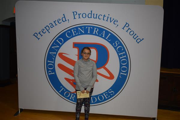 One student posing with Eye of the Tornado award in front of sign showing the Poland logo and slogan