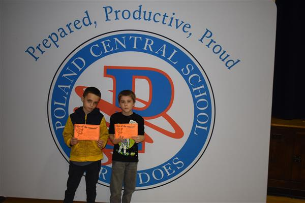 Two more students posing with their Eye of the Tornado awards in front of sign showing the Poland logo and slogan