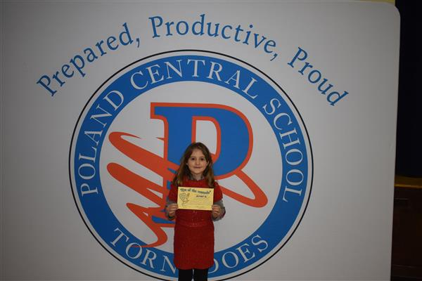 One student posing with her Eye of the Tornado award in front of sign showing the Poland logo and slogan