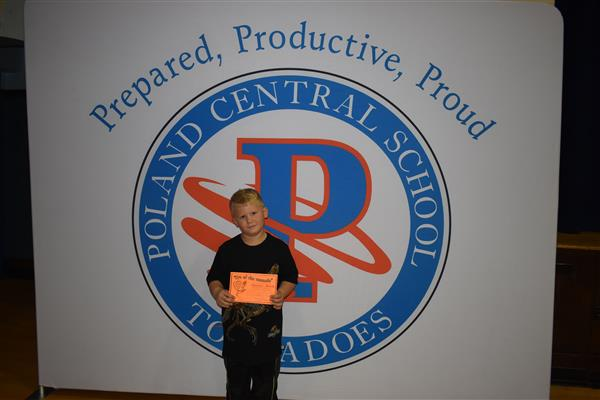 One student posing with his Eye of the Tornado award in front of sign showing the Poland logo and slogan