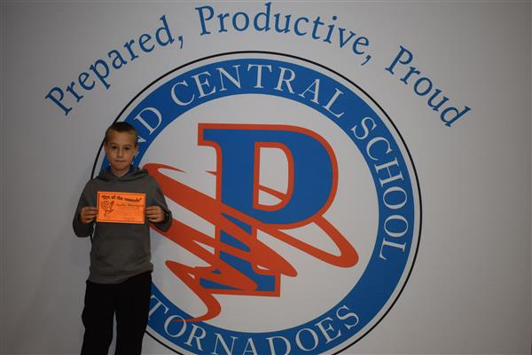 Another student posing with his Eye of the Tornado award in front of sign showing the Poland logo and slogan