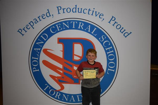 One more student posing with his Eye of the Tornado award in front of sign showing the Poland logo and slogan
