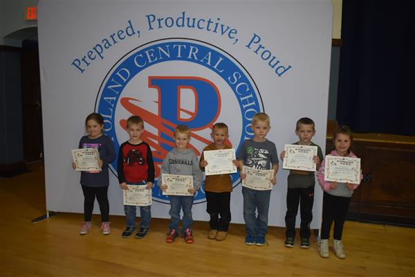 Seven students holding Attendance Hero awards in front of sign showing the Poland logo and slogan