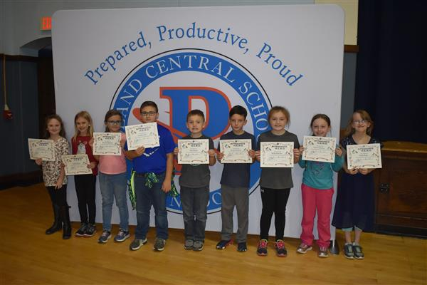 Nine students holding Attendance Hero awards in front of sign showing the Poland logo and slogan