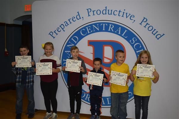 Six students holding Attendance Hero awards in front of sign showing the Poland logo and slogan