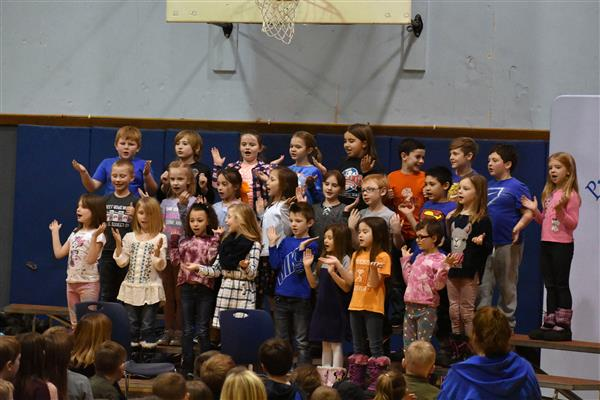 Second-graders singing at school assembly