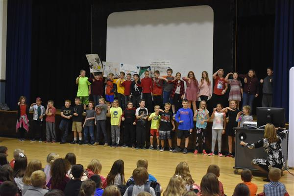 Fifth-graders dance and sing on stage