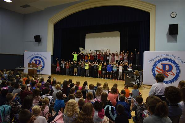 Fifth-graders singing and dancing on stage as other elementary students look on
