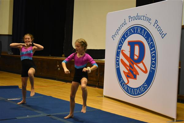 Two students perform gymnastics