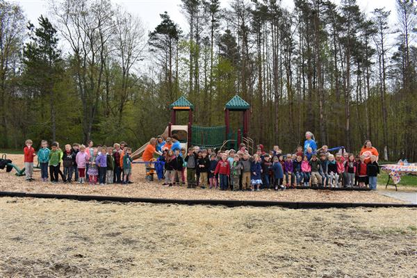 Playground ribbon cutting with teachers and students.