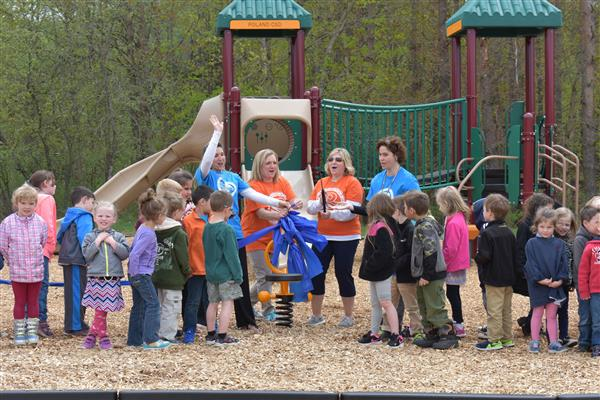 Prekindergarten and kindergarten teachers cut a ribbon for the new playground.