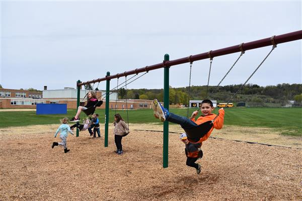 Students ride on new swingset.