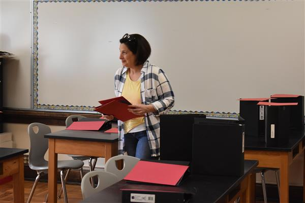Mrs. Zuchowski sets out school supplies in her new classroom