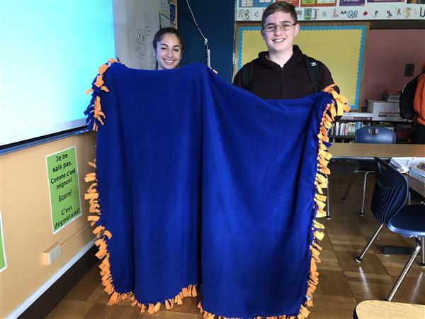 Two students holding an orange and blue blanket they made in French Club