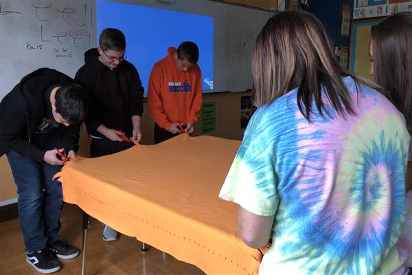 Poland French Club members work on making an orange and blue blanket in class