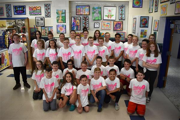 A large group of elementary students pose in the cafeteria wearing pink and white shirts