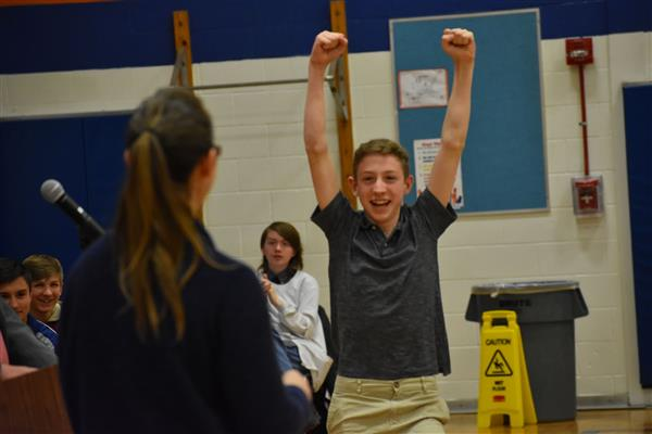 Student with both arms in the air celebrating winning grand championship